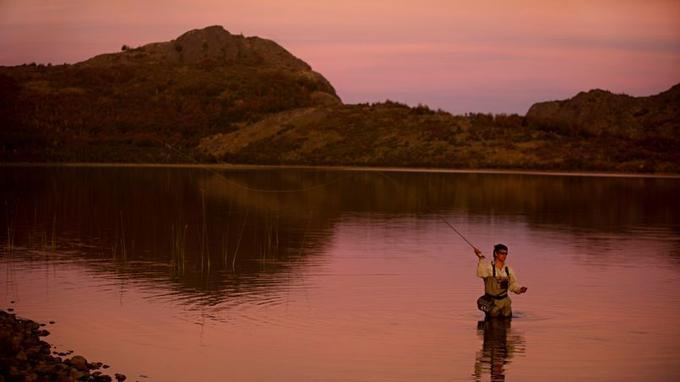 Au coucher du soleil, un guide de pêche de l'estancia Tres Valles pêche à la mouche dans le lac principal de la propriété.