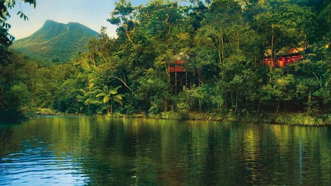 Vue sur les cabanes construites près d'une rivières ou l'on peut faire du canoë (Crédit: Silky Oaks Lodge)