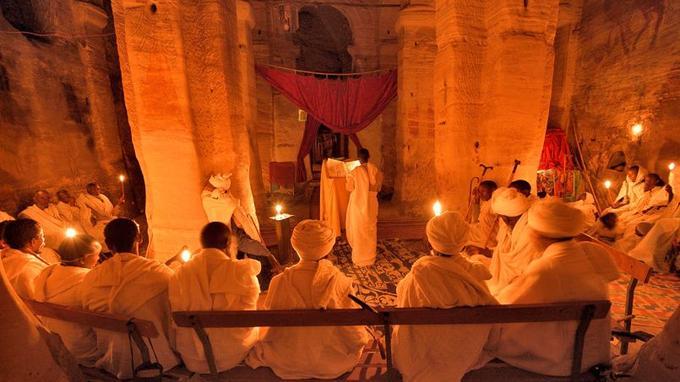 Assis dans le déambulatoire, les hommes se sont mis à prier tandis que la voix du prêtre lisant les textes sacrés résonne dans l'église rupestre Maryam Korkor.