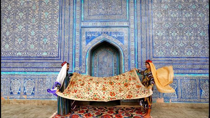 Jeunes filles en tenue traditionnelle exposant des suzanis dans le complexe de la Koukhna Ark, ancienne résidence fortifiée des khans, les seigneurs de Khiva.