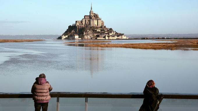 Des touristes admirent le Mont-Saint-Michel ce dimanche, encerclé par la mer.