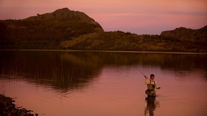 Ao pôr-do-sol, um guia de pesca da estância Tres Valles pesca com mosca no lago principal da propriedade.'estancia Tres Valles pêche à la mouche dans le lac principal de la propriété.