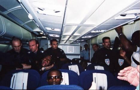Des policiers français tentent le 11 août 2004 de faire sortir  d'un avion de la compagnie Air France une Sénégalaise qui proteste  contre les mauvais traitements subis par un Malien en voix d'extradition  à l'aéroport de Roissy.
