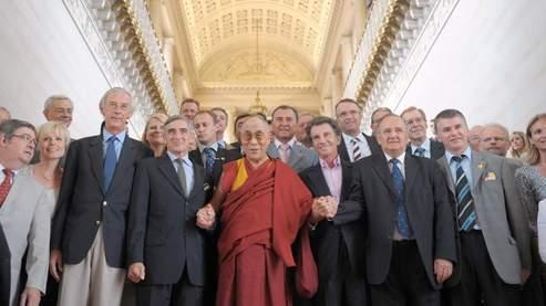 Le dalaï-lama, main dans la main avec les parlementaires français qui l'ont reçu mercredi au Sénat. (Olivier Laban-Mattei / AFP)