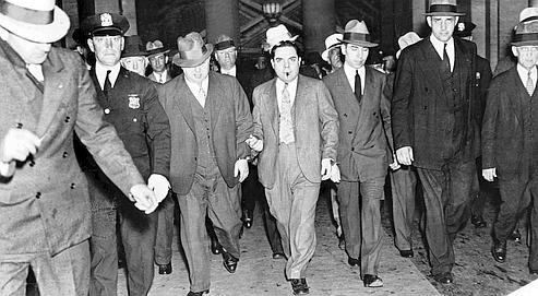 Arrêté en 1936, Lucky Luciano (au centre, avec les menottes et le cigare) avait su tirer profit de la prohibition pour mener une existence fastueuse et devenir en quelques années le «roi du crime» aux États-Unis (photo ©Rue des Archives/PVDE).