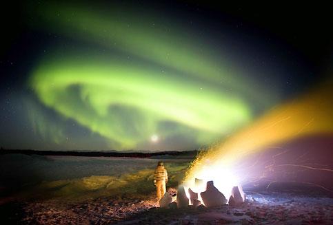 Telle une immense draperie ondulante, cette aurore boréale serpente lentement dans le ciel glacé de l'Alaska. Magique, sa lumière froide semble jouer avec les flammes du brasier allumé en plein vent. Ce spectaculaire phénomène atmosphérique, appelé aurore boréale dans l'hémisphère Nord et aurore australe dans l'hémisphère Sud, est caractérisé par des ondulations extrêmement colorées dans le ciel nocturne, le vert et le rouge étant prédominants. Provoquées par l'interaction entre les particules chargées du vent solaire et la haute atmosphère, les aurores se produisent principalement dans les régions proches des pôles, entre 65 et 75 ° de latitude.