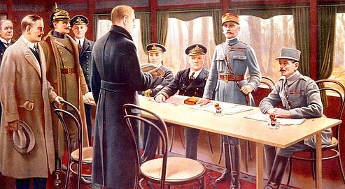 La signature de l'armistice, dans un wagon à Rethondes, par le maréchal Foch (debout à droite) et les plénipotentiaires allemands. (Rue des Archives / Tal)
