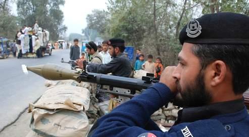 Des officiers de la police pakistanaise sont en état d'alerte, à un croisement à Shabqadar, à 30 kilomètres au nord de Peshawar, le 12 novembre. Un attentat-suicide venait d'y faire 3 morts à l'entrée d'une école.