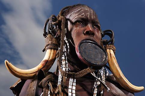 Cette femme est une Mursi. Elle vient d'un monde où la crise financière qui menace l'économie mondiale n'existe pas. Un monde où les mots mondialisation, terrorisme et subprimes n'ont encore aucun sens. Les Mursi vivent au bord du fleuve Omo dans le sud-ouest de l'Ethiopie. Dans cette vallée encaissée qui fait le bonheur des photographes et des anthropologues du monde entier, les femmes continuent à porter fièrement un plateau d'argile à travers leur lèvre inférieure incisée. De nombreuses ethnies d'agriculteurs et d'éleveurs survivent encore dans la vallée de l'Omo, à l'image des Karo, des Surma ou des Galeba. Pour combien de temps ?