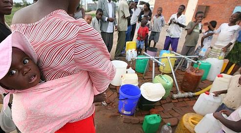 Une femme et son enfant attendaient pour obtenir de l'eau, lundi, à Harare. L'Europe demande l'intervention de l'OMS contre une épidémie de choléra qui a déjà «probablement fait des milliers de victimes». (AP/Tsvangirayi Mukwazhi)