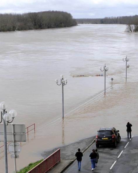 Des promeneurs viennent mesurer la montée des eaux de la Garonne à Cadillac (Gironde). Après les vents de la tempête Klaus atteignant par endroit les 190 km/h, les inondations ont à leur tour menacé habitations et infrastrutures.