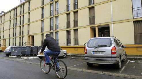 Une personne passe en vélo devant l'immeuble HLM de Montluçon où deux nouveaux-nés ont été retrouvés morts lundi dans une cave.