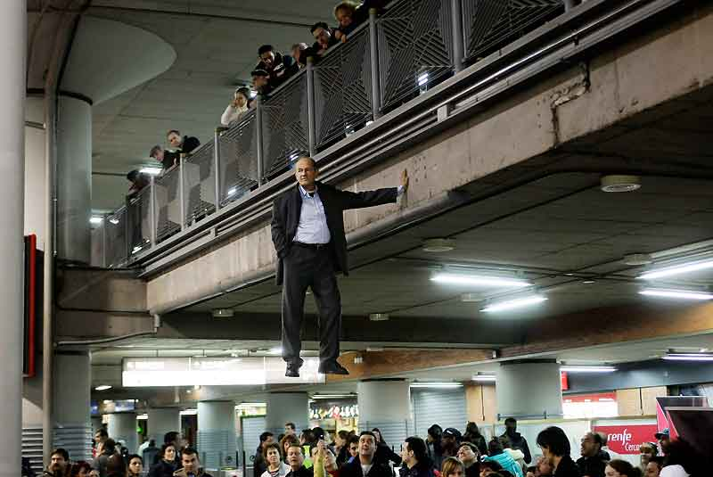 Depuis des années, l'artiste illusionniste allemand Johan Lorbeer défie la gravité au cours de sa performance intitulée «Tarzan», exécutée ici à Madrid dans la gare d'Atocha, le 10 février dernier. Ses longues apparitions accroché à un pont ou à la façade d'un immeuble ont fait le tour du monde et largement contribué à sa célébrité. Mais quel est son secret ? En fait, Johan Lorbeer est tout simplement soutenu par une fausse main de fer fixée sur la paroi et assujettie à un harnais dans lequel se glisse l'artiste. Sans aucun effort, il peut ainsi, en toute décontraction, rire au nez de la pesanteur et du public joliment berné, et charmé à la fois.