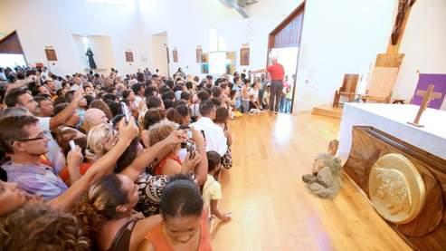 Des milliers de fidèles se recueillent ou prennent une photo du mystérieux coussin... Crédit photo : AFP.