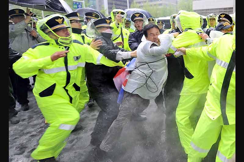 À Seoul, devant le ministère des Affaires étrangères, un activiste conservateur sud-coréen se bat avec les policiers qui tentent de retirer un drapeau nord-coréen, lors d'une manifestation visant à soutenir les sanctions des Nations Unis contre la Corée du Nord.