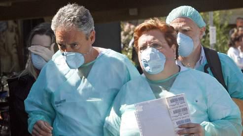 Ces employés du CHU de Valence (Espagne), où est hospitalisé un des cas suspects de grippe porcine, redoublent de précautions.