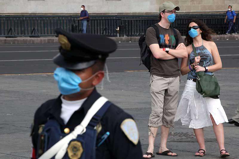 Mexico, sur la place Zocalo .Comme les officiers de police, des touristes portent un masque pour se protéger du virus de la grippe porcine. Les tours opérateurs allemands et japonais ont suspendu leur voyages au Mexique..