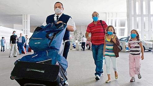 Une famille à l'aéroport de Mexico. Les étrangers sont nombreux à se hâter de quitter le pays, dans la crainte de nouvelles restrictions ou annulations de vols après l'alerte de l'OMS.