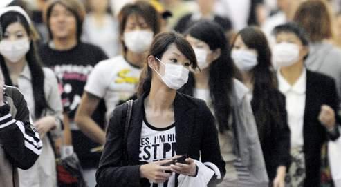 Ces passants d'une rue commerçante de Kobé portent presque tous des masques. Les industriels du secteur enregistrent des hausses records à la Bourse de Tokyo.