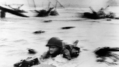 Plage d'Omaha Beach, 6 juin 1944. Les troupes américaines se jettent à l'eau. A minuit, 132 000 soldats alliés auront débarqué sur les plages de Normandie ; 10 500 seront morts avant d'avoir touché terre.