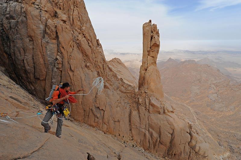 Pose d'un rappel pour atteindre le pied de la Takouba. A plus d'une journée de marche de leur campement, les grimpeurs évoluent en autonomie dans l'univers stérile du Hoggar algérien.