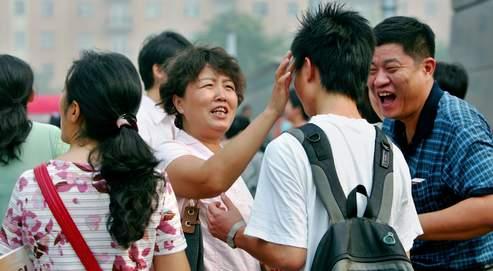 Une mère enduit les tempes de son fils avec des herbes médicinales juste avant le début de l'examen-concours. Après avoir passéles épreuves du Gaokao, les étudiants sont classés selon un système de points qui conditionne leur entrée à l'université.