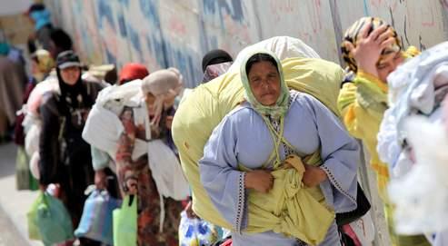 Des Marocaines, transportant des fardeaux qui pèsent jusqu'à 70 kilos, font la queue au poste de frontière de Biutz.