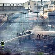 Un pompier refroidit à la lance à eau une citerne de gaz.