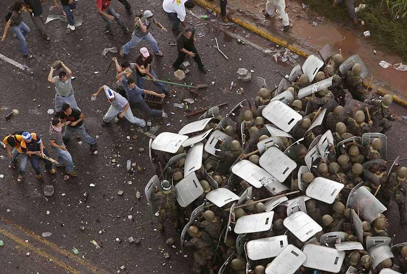 Un golpe, en espagnol, c'est un coup, et même un coup d'État; et Tegucigalpa, la capitale du Honduras, en est coutumière. Ces affrontements se sont produits lundi dernier, au lendemain de l'expulsion du chef de l'État, Manuel Zelaya, par l'armée hondurienne, soutenue par les congressistes et les juges de la Cour suprême de cette République qui peine à accepter les règles de la démocratie, après des décennies de dictature militaire. Zelaya n'était «coupable» que d'avoir voulu organiser un référendum, un procédé que l'armée a jugé «antidémocratique». Mais il compte bien récupérer le pouvoir, fort du soutien de la rue et de tous les chefs d'État d'Amérique, de Hugo Chavez à Barack Obama.