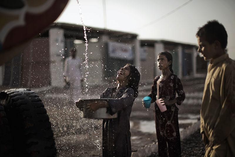 Une petite réfugiée pakistanaise reçoit de l'eau apportée par les équipes humanitaires de l'UNHCR dans un camp de fortune près de Peshawar. Plus de trois millions de personnes ont fui les combats contre les talibans dans les provinces du SWAT.