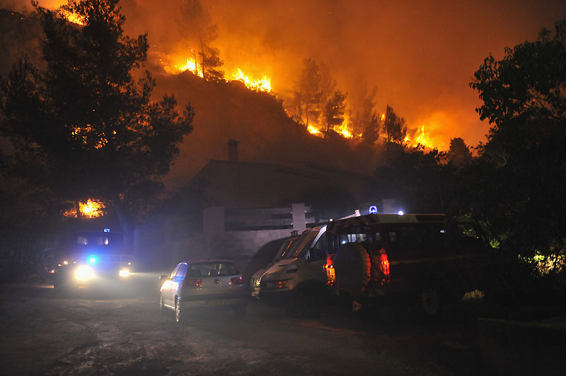 Des véhicules de pompiers stationnent près d'une maison menacée par un incendie qui s'est déclaré aux portes de Marseille, mercredi soir. Quelques dizaines de maisons ont brûlé dans le quartier des Trois-Ponts, à l'est de Marseille, dans un feu qui a détruit 1.200 hectares.