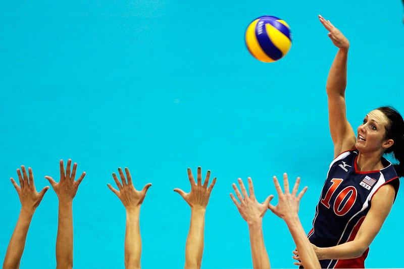 La volleyeuse américaine Kristin Richards effectue un smash face au rideau défensif des Allemandes, lors d'un match à Rio de Janeiro.