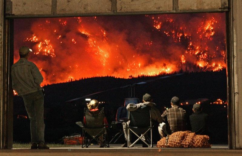 Des pilotes canadiens d'hélicoptères observent le 4 août des feux de forêts que les pompiers laissent volontairement brûler pour tenter de limiter la violence des incendies de la montagne Lillooet, en Colombie britannique. Deux mille cinq cents personnes ont pour l'instant été évacuées.
