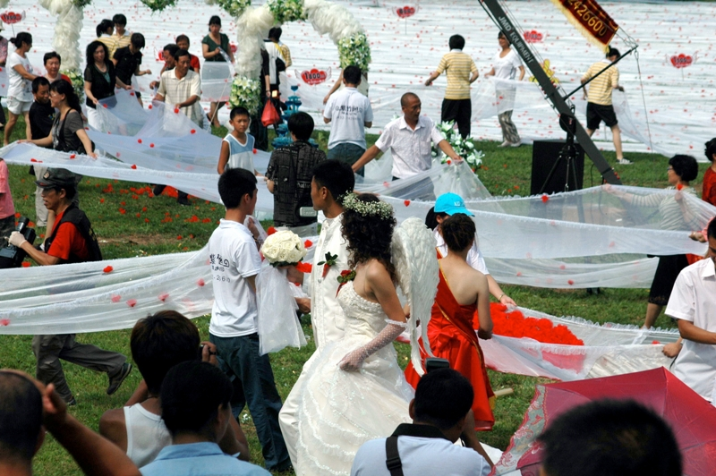 Une mariée chinoise tire derrière elle une traîne de 2 162 mètres de long dans un parc de Jilin, le 6 août. Zhao Peng, le marié, et sa famille ont passé près de deux mois à coudre ensemble les différentes parties de la traîne, commandées spécialement dans une usine avec l'objectif de battre l'actuel record de 1 579 mètres.