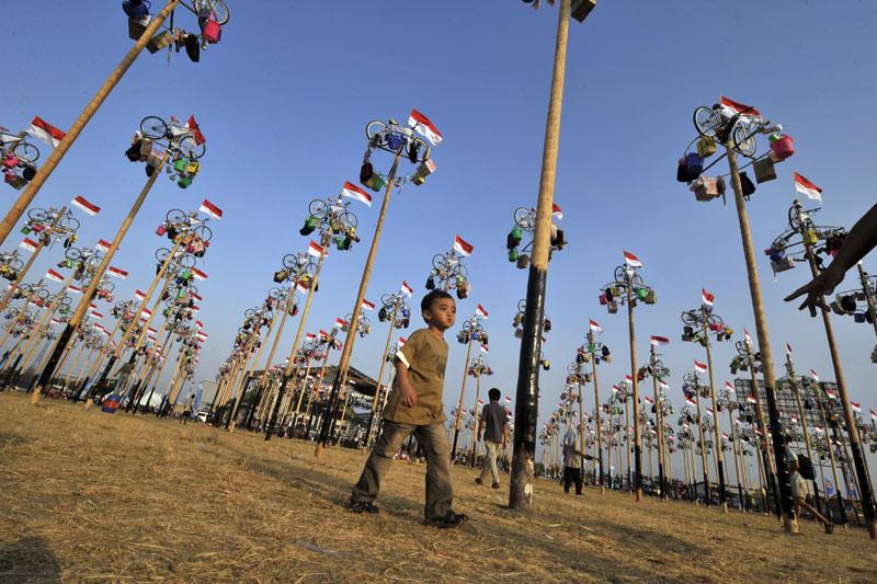 Jour de festivité original en Indonésie pour célébrer le 64e anniversaire de l'indépendance. Dans un grand parc de la capitale Jakarta, on a hissé vélos, jouets divers et cadeaux surprises en haut de plusieurs centaines de mâts. Pour obtenir leur récompense, les habitants doivent eux-mêmes la décrocher…