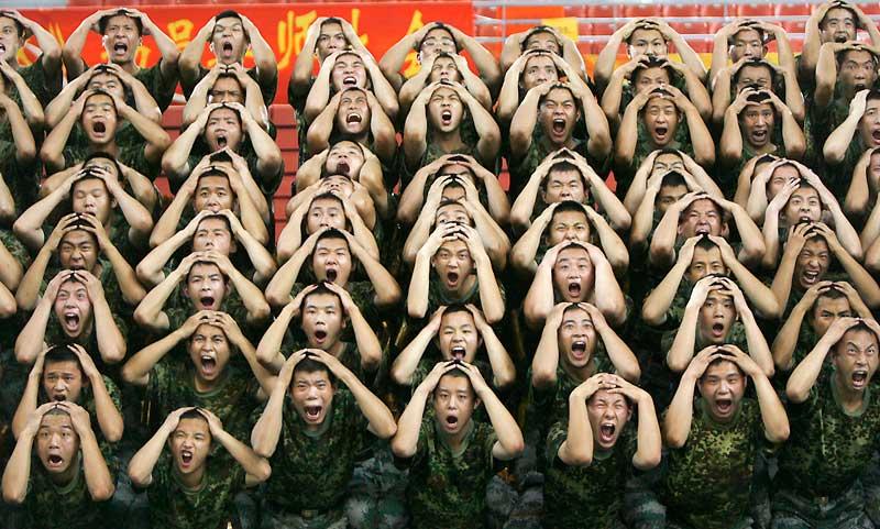 Aucune terrible nouvelle ne vient de tomber. La Terre tourne toujours sur son axe et le Soleil se lèvera demain. Pas d'inquiétude, rassurez-vous. Ceci n'est pas non plus un concours de la plus belle grimace. Ou du plus fort hurlement de terreur au monde. Tout simplement, ces soldats de l'Armée populaire chinoise de libération, en treillis de camouflage, sont en pleine répétition d'une comédie musicale géante qui sera présentée en octobre prochain à Pékin pour célébrer le soixantième anniversaire de la fondation de la Chine communiste. On ne sait cependant pas à quel tragique événement correspondent ces faces de carême.