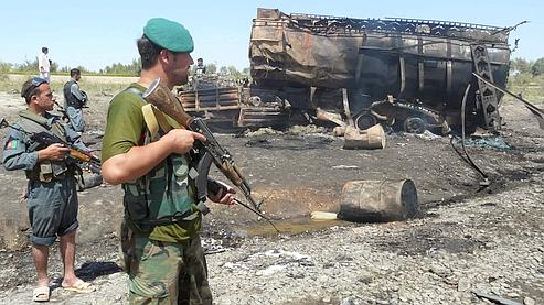Un agent de sécurité afghan se tient près d'un camion-citerne brûlé à Kanduz, au nord de Kaboul vendredi.