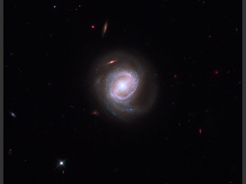 <b>La galaxie «Markarian 817».</b><br /> Des anneaux d'étoiles bleu vif entourent le coeur –actif et très lumineux– de la galaxie. Au centre, un trou noir colossal (40 millions de fois plus gros que notre Soleil) expulse d'énormes quantités de matière vers l'extérieur à plus de 9 millions de kilomètres par heure. Les nouveaux outils de Hubble ont permis sur cette image de mettre en évidence ces rejets de matière.