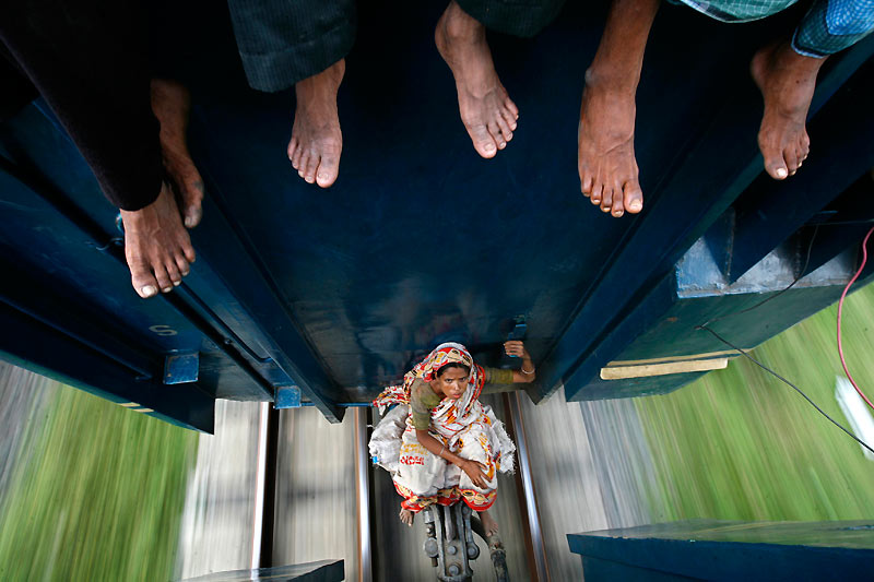 Cette jeune habitante de Dacca, au Bangladesh, est obligée de voyager entre deux wagons dans une position pour le moins inconfortable... et périlleuse. Elle fait partie des millions de Bengalais qui ont quitté la capitale, samedi dernier, afin de rejoindre leur famille pour fêter la fin du ramadan. L'Aïd-el-Fitr se célèbre par des pétards et des feux d'artifice ainsi que par toute une série de rituels religieux. Les fidèles sont notamment tenus de prendre un bain, manger un nombre impair de dattes, revêtir leurs plus beaux habits, s'en aller prier, échanger des voeux, et revenir de la mosquée en empruntant un chemin différent de celui pris à l'aller.
