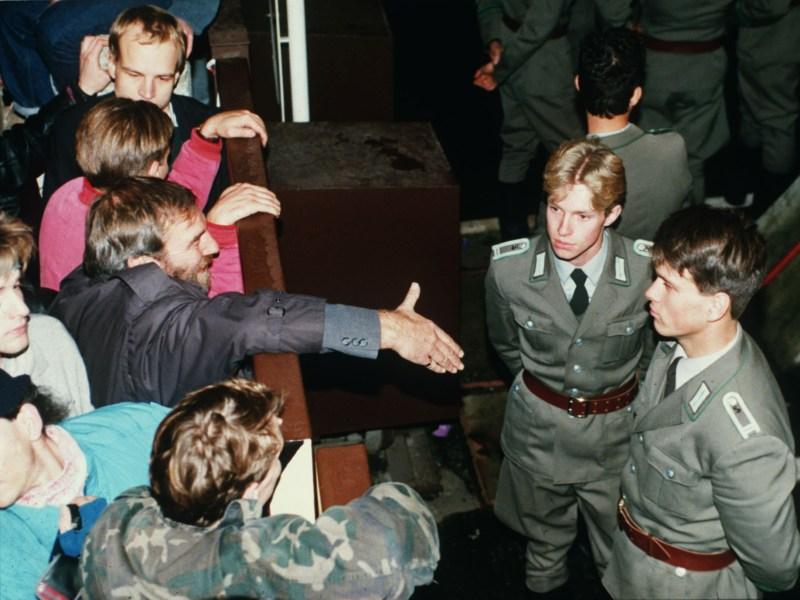 Deux policiers est-allemands refusent de serrer la main des Berlinois.