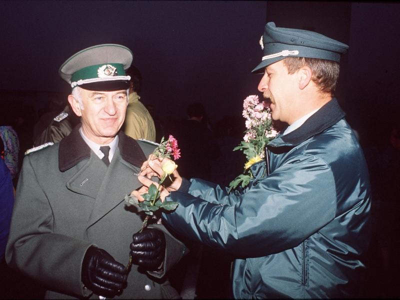 Des policiers de RDA et RFA échangent des fleurs.