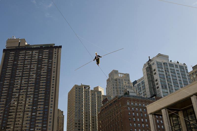 Performance du funambule, Bello Nock, qui exécute un acte d'équilibriste sur une corde raide tendue entre deux immeubles au-dessus de la grande place du Lincoln Center, à New York, mardi 6 octobre, à l'occasion de la venue de la «Big Apple Circus».