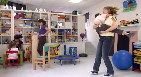 Une éducatrice porte un enfant autiste, en septembre dernier à Paris.