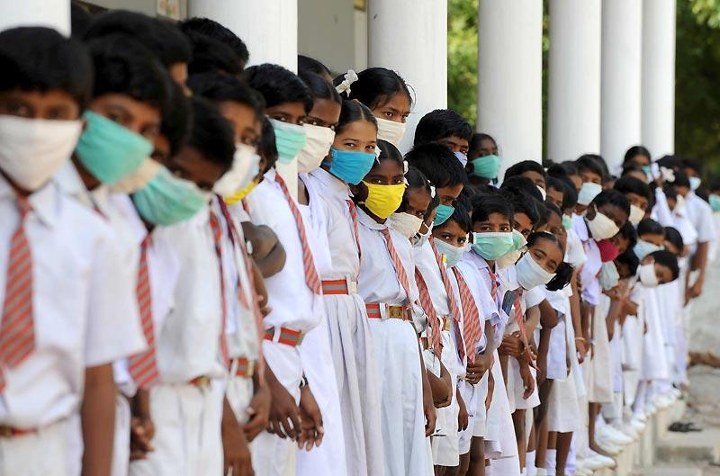 Suite aux terribles inondations dans la région du Mahaboobnagar, en Inde, 300 personnes sont mortes et plus d'un million d'habitants ont du être déplacés. Ici, des écoliers du village de Shanti Nagar portent un masque pour éviter toute propagation d'épidémie, le 10 octobre.