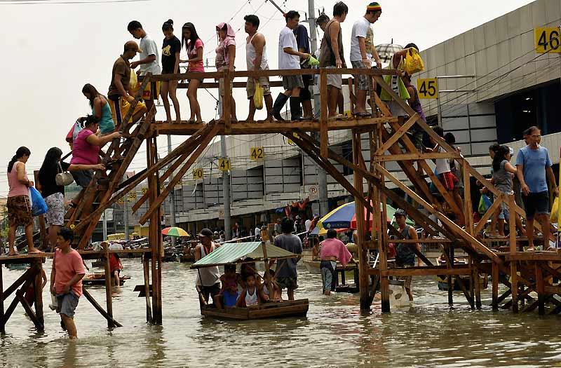 Le bilan des intempéries qui ont frappé les Philippines le mois dernier s'élève à près d'un millier de morts, alors qu'un nouveau typhon menace l'archipel. Les habitants s'organisent et construisent des ponts de fortune pour traverser des rues encore inondées, comme ici, samedi 17 octobre.
