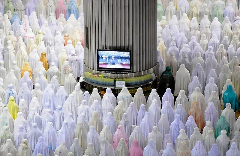 Située au coeur de l'une des villes les plus bruyantes et surpeuplées de l'Asie du Sud-Est, la mosquée Istiqlal (indépendance) de Jakarta, en Indonésie, est une véritable oasis de calme et de fraîcheur. Dans certaines grandes occasions, comme ici, elle peut accueillir 150 000 fidèles, dont une forte proportion de femmes, séparées des hommes par des panneaux en bois sur roulettes. Il avait fallu dix-sept ans pour la construire avant son ouverture en 1978, mais depuis, elle n'a jamais cessé d'être modernisée. Chacun de ses douze piliers est ainsi équipé d'un écran plasma qui retransmet le prêche de l'imam, ainsi que d'étagères garnies d'exemplaires du Coran.