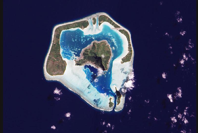 Cette image impressionnante de l'île de Maupiti, en Polynésie française, a été réalisée par un satellite de la Nasa le 8 août. L'ilôt central est entouré d'un superbe lagon aux eaux turquoise, délimité par les longilignes îles périphériques et des récifs coralliens. <br />Principal point de contact de l'île avec le monde extérieur, la piste d'atterrissage est clairement visible au nord-est, coupant en ligne droite à travers forêts et récifs coralliens.
