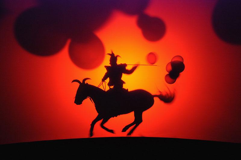 En ombre chinoise, un cavalier du nouveau spectacle de Bartabas, présenté depuis le 4 décembre au Théâtre équestre Zingaro au fort d'Aubervilliers (Seine-Saint-Denis). Baptisé Darshan qui signifie «vision du divin» en sanscrit, son nouvel opus est conçu comme un gigantesque théâtre d'ombres circulaire, «en proie à un étrange mouvement continu qui entraîne le public dans une douce gravitation», selon les mots de Bartabas, qui fête aussi les 25 ans de Zingaro. Pour la première fois, l'homme a choisi de demeurer dans son théâtre de bois et d'y rester pour toute la saison 2009-2010, au lieu de faire le tour du monde avec chapiteaux, chevaux et caravanes.