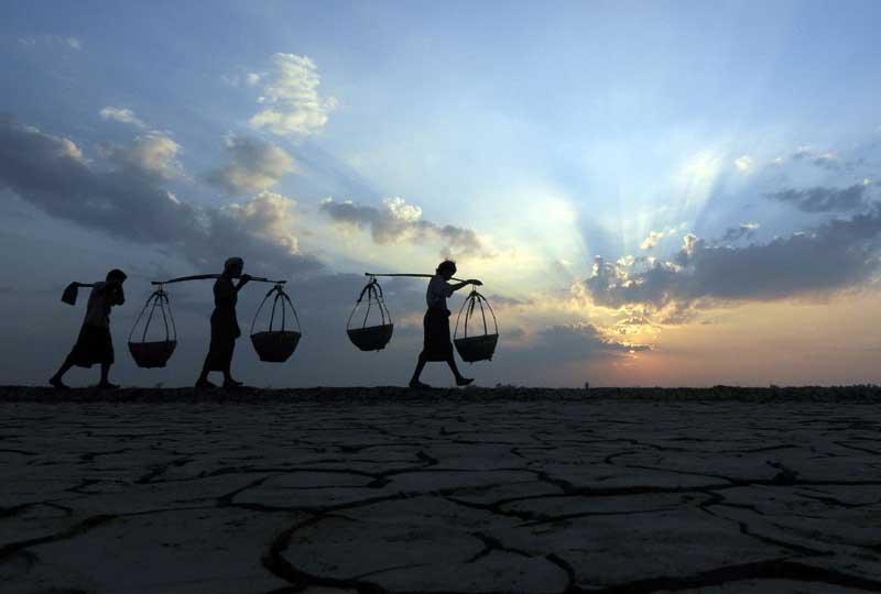 Birmanie, après le passage du cyclone Nargis. Des villageois portent leur récolte de sel près du village de Ohn-chaung. Les gisements de sel sont en pleine reconstruction après avoir été totalement détruits en mai 2008.