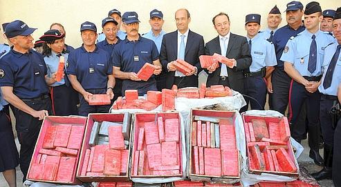 Le ministredu budget, Éric Woerth, pose le 29 mai 2009 à Montpellier, aux côtés des douaniers, devant 684 kg de cocaïne saisis dans un poids lourd sur l'autoroute A9.
